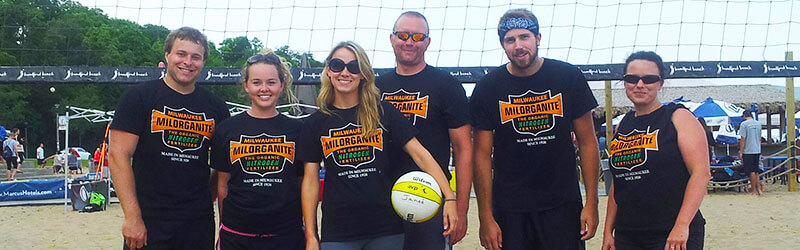 Individuals playing volleyball in Milorganite tshirts