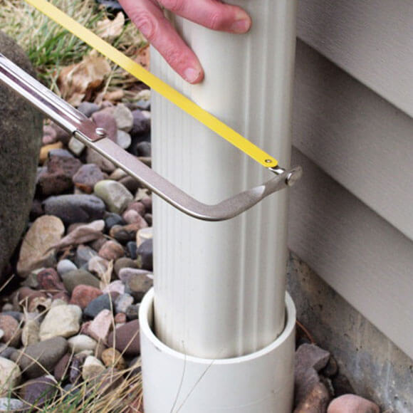 man cutting downspout